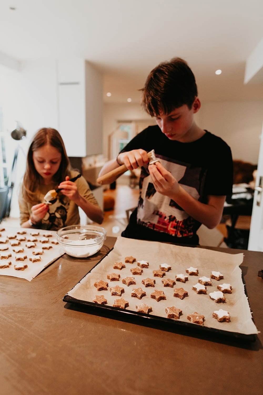 young girl and boy - siblings - baking german cinnamon stars for Christmas