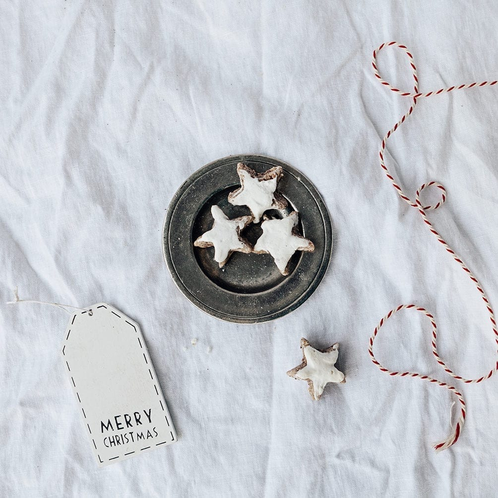 homemade cinnamon stars after a german recipe on a white layflat and a merry christmas sign