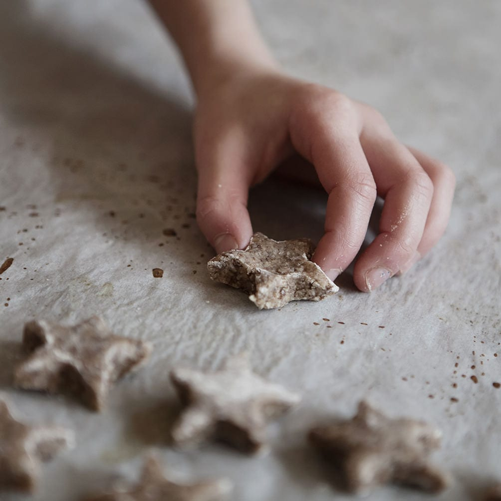 hand placing a homemade cinnamon star after a german recipe on a baking sheet