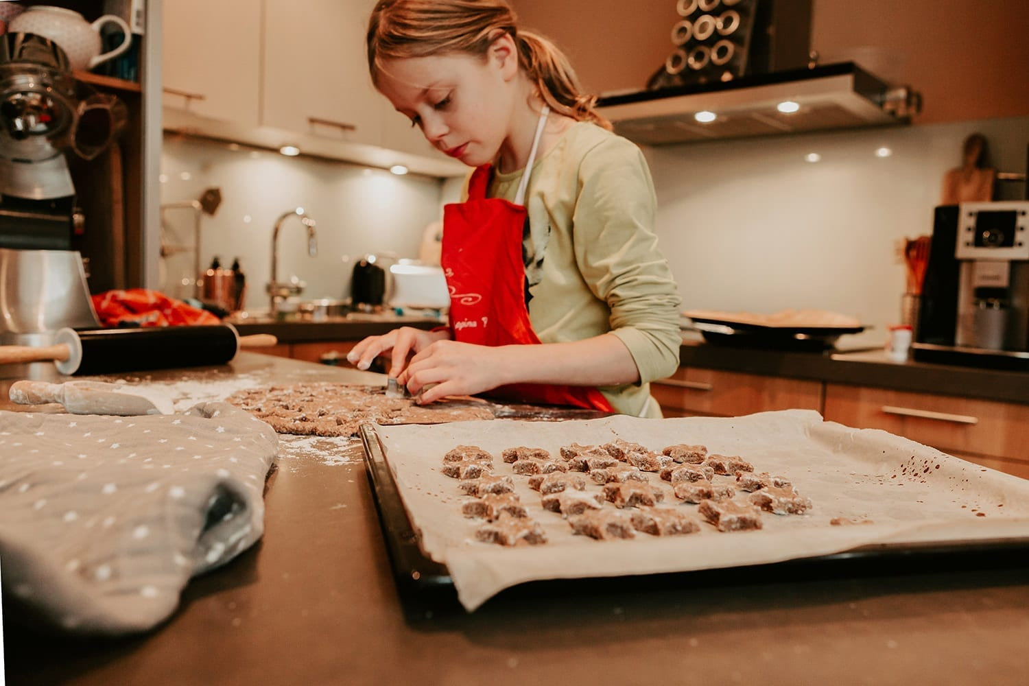 young girl with a red apron baking german cinnamon stars for Christmas