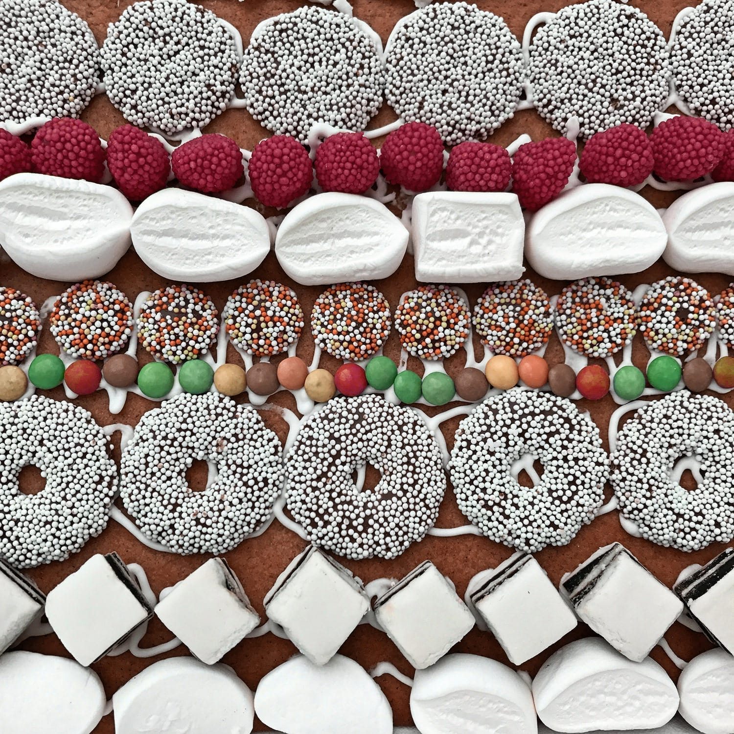 colorful Sweets on a homemade scandinavian gingerbread house
