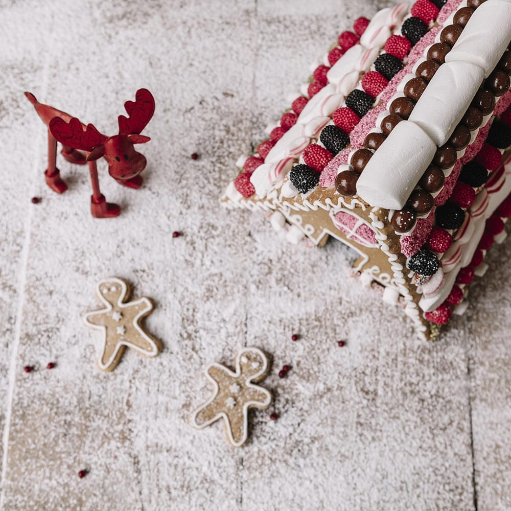 homemade scandinavian gingerbread house with lots of sweets on a snowy surface and with gingerbread men