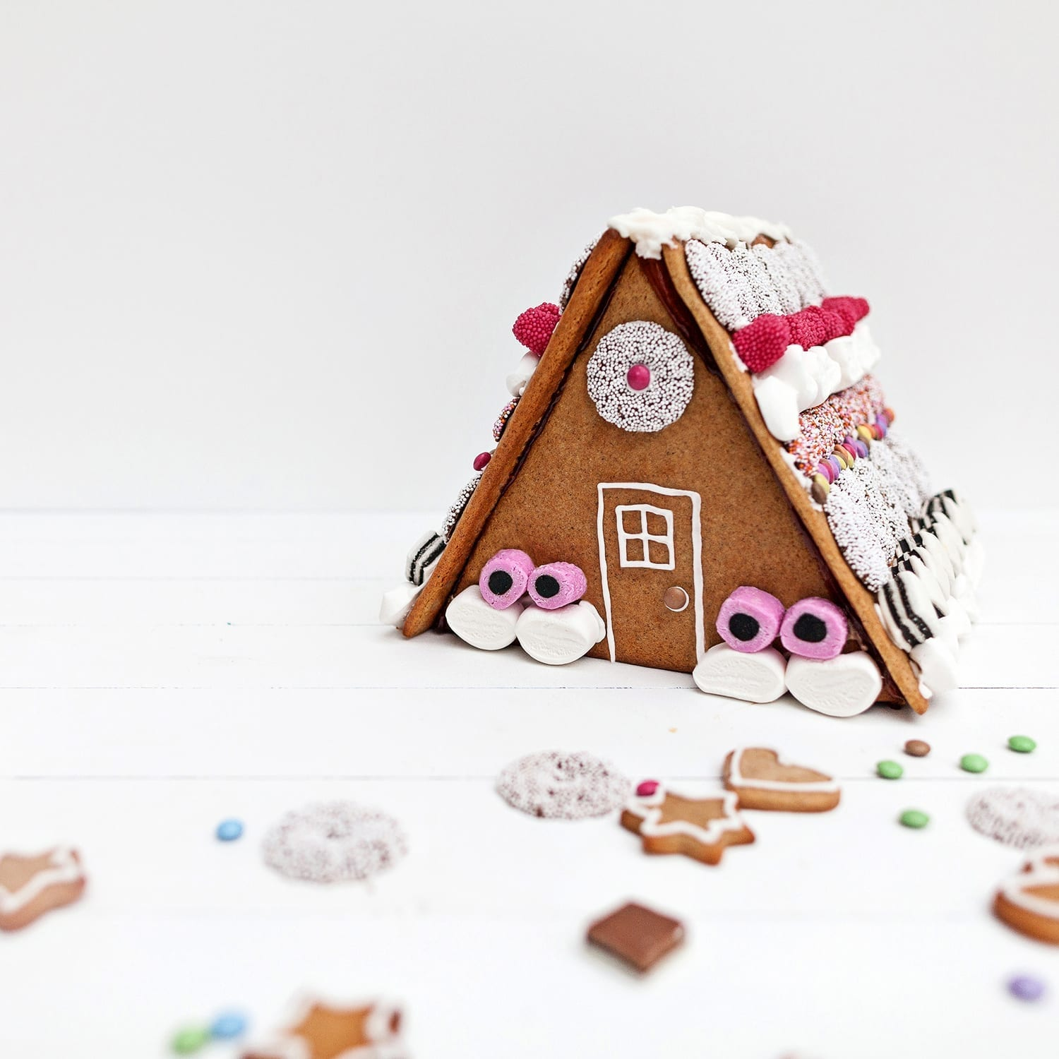 homemade scandinavian gingerbread house with lots of sweets on a white surface and with gingerbread men