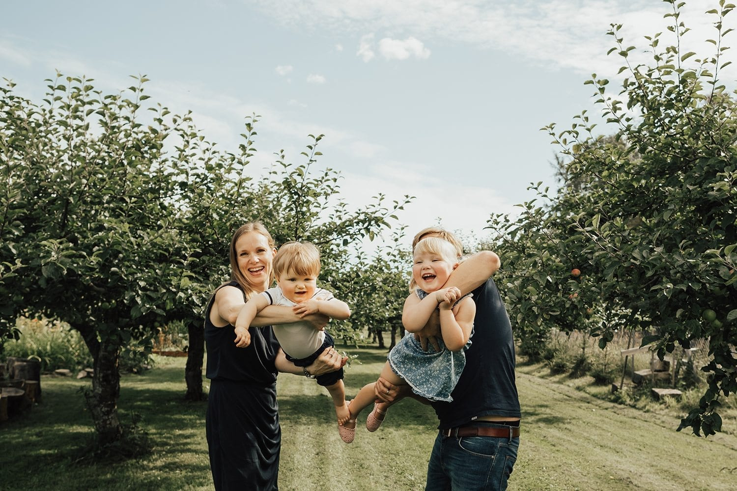 Outdoor lifestyle family shoot in Norway, four people amongst apple trees