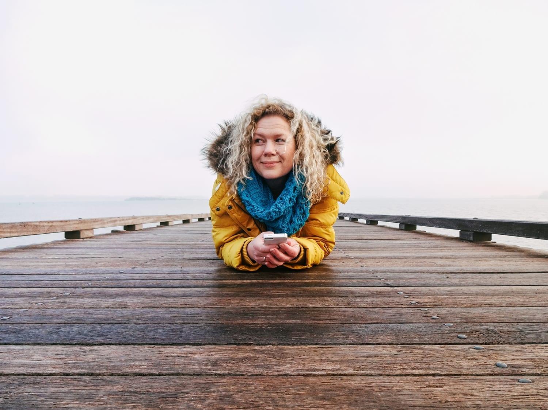 Self portret van marianne hope op een pier in huizen Nederland vrouw met gele jas