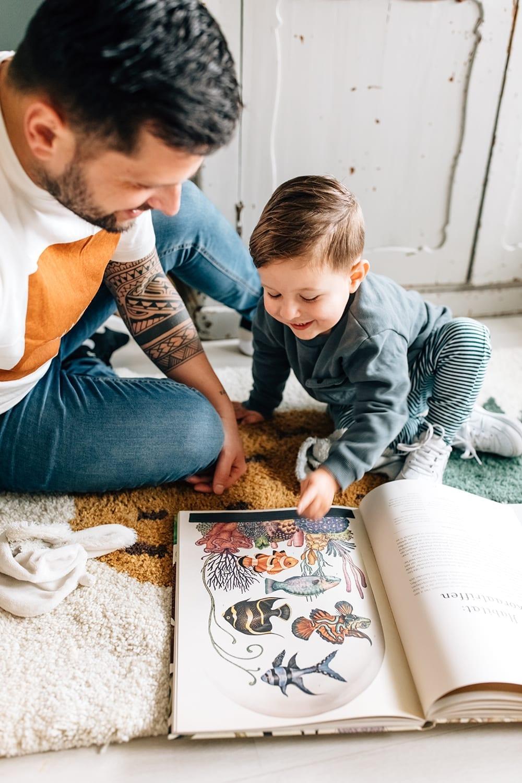 thuis familie fotosessie met vader die leest voor voor zijn zoon