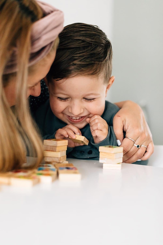 moeder speelt met lachende zoon in een thuis familie fotosessie