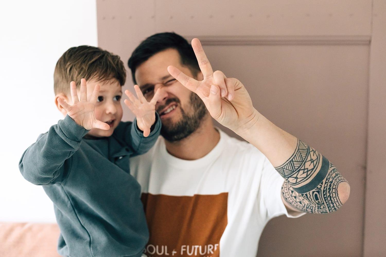 doorkijkfoto in thuis familie fotosessie met vader die speelt met zijn zoon
