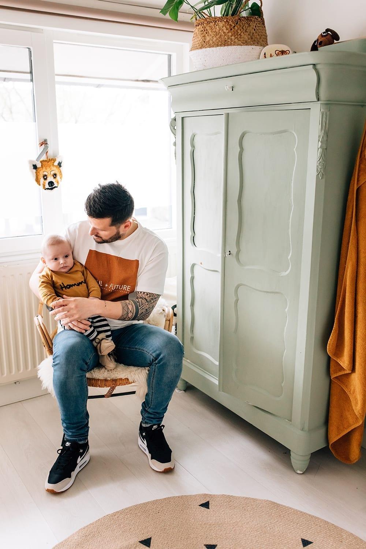 doorkijkfoto in thuis familie fotosessie met vader en baby zoon op de babykamer