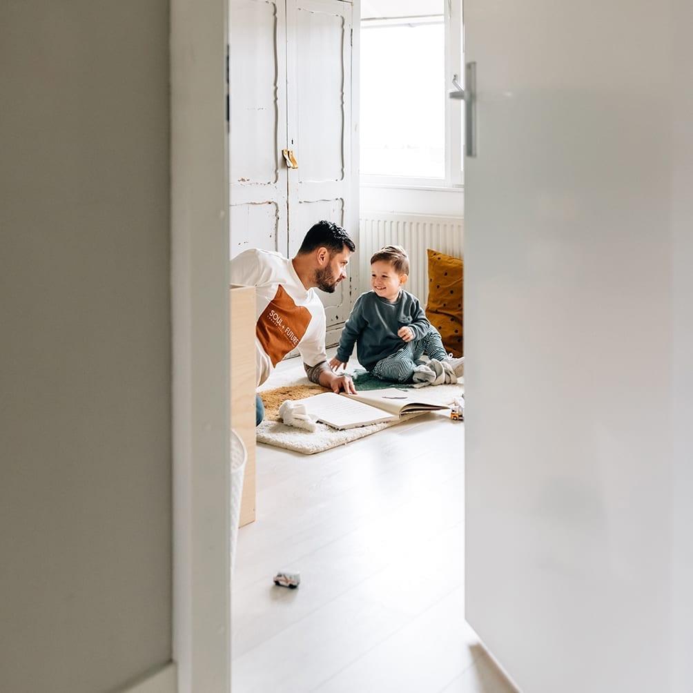 doorkijkfoto in thuis familie fotosessie met vader die speelt met zijn zoon op de kinderkamer