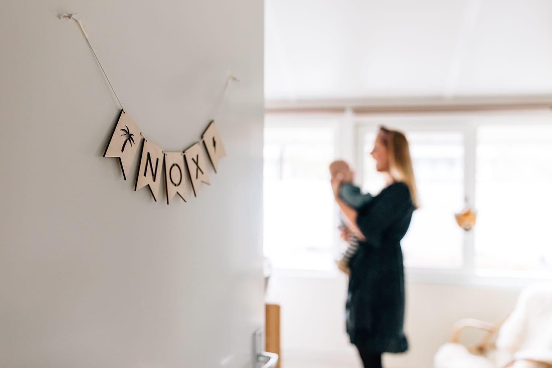 doorkijkfoto in thuis familie fotosessie met moeder en baby zoon op de babykamer