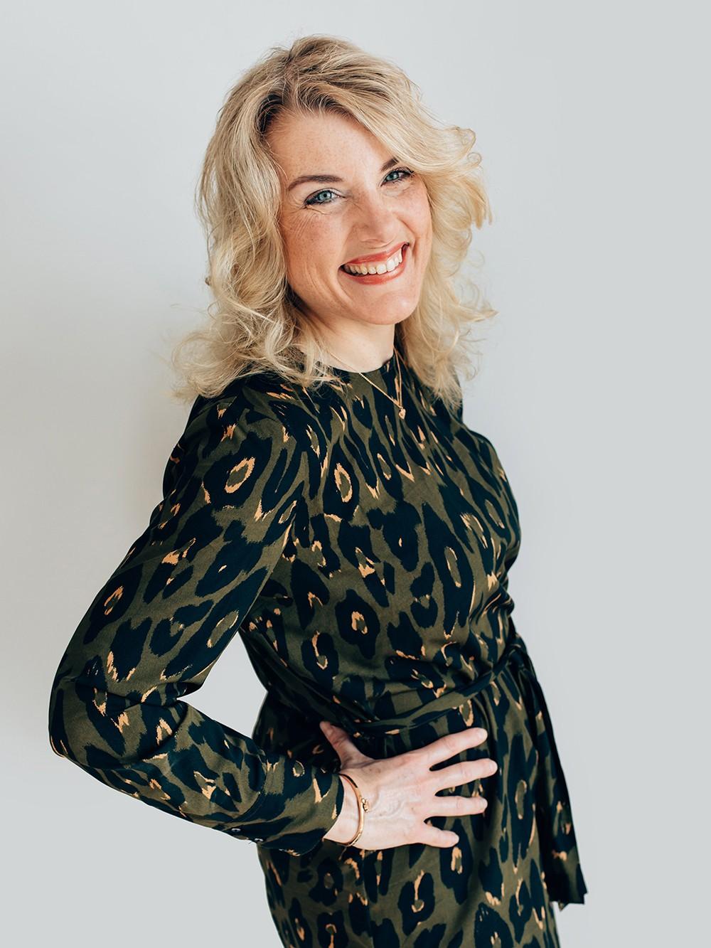 gelukkig lachend blonde vrouw portret met witte achtergrond en wind in haar haar voor professionele personal branding