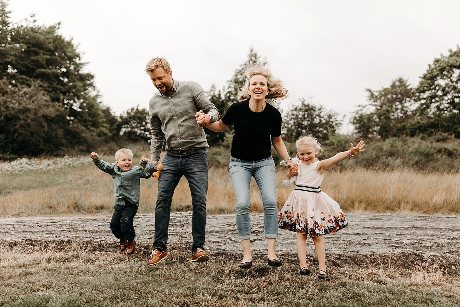 outdoor lifestyle family session with two kids jumping and having fun
