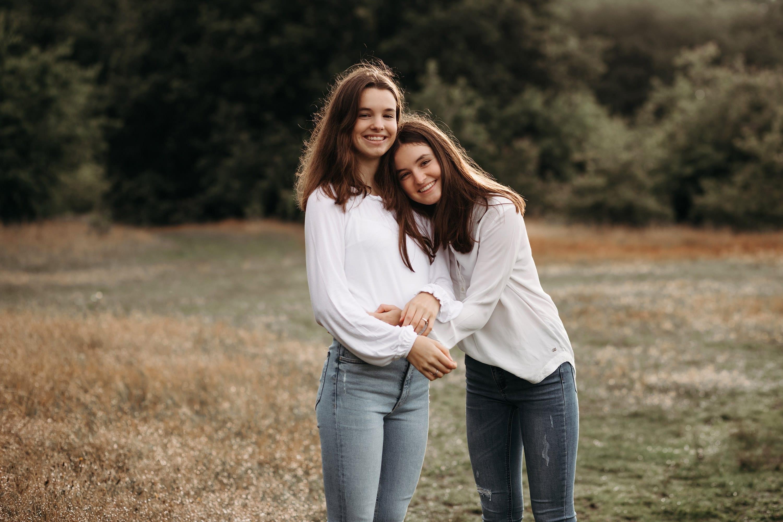 zusterliefde in een zussen fotosessie buiten in de Nederlandse natuur