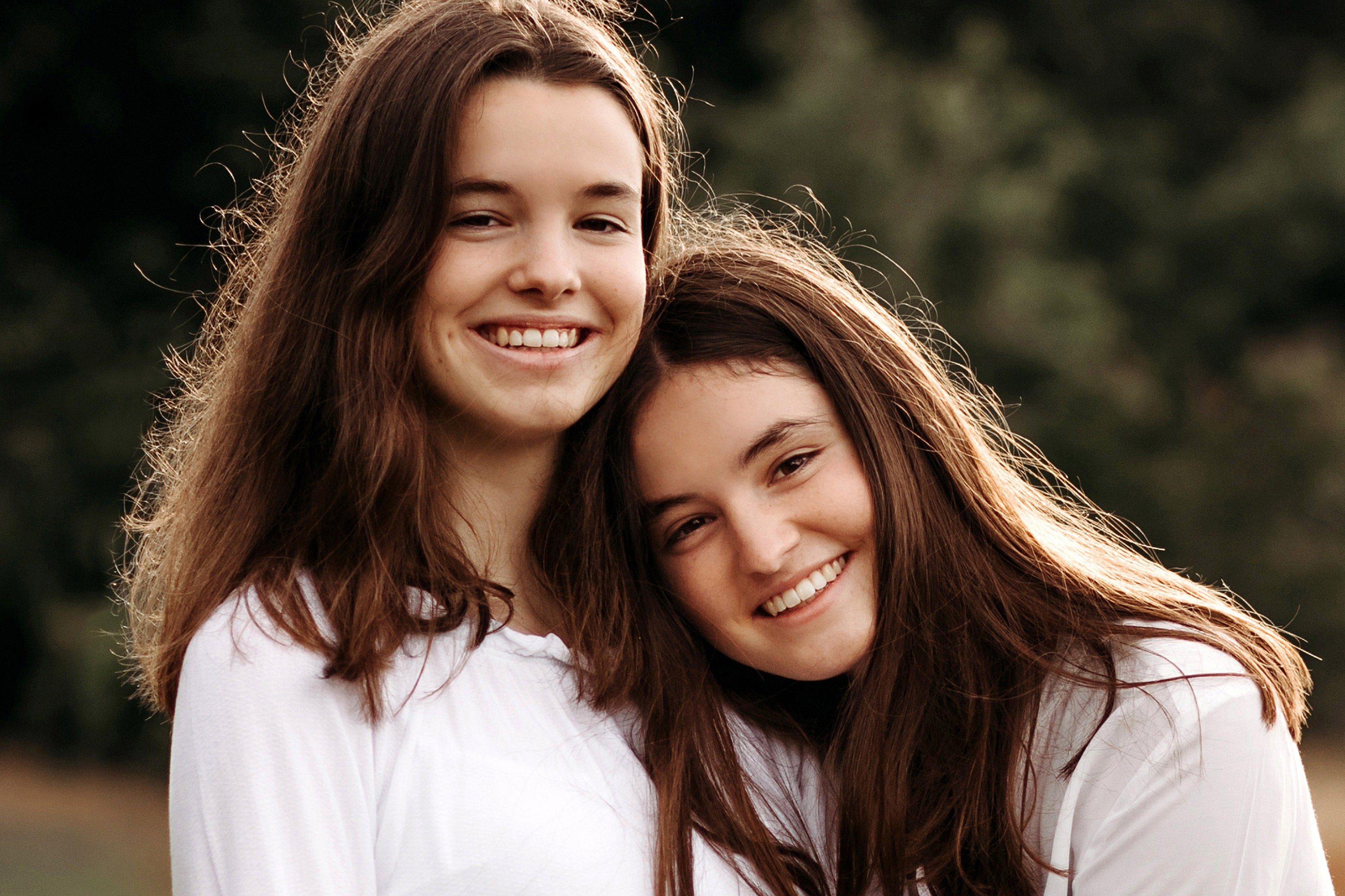 Two brown-haired and smiling young sisters posing in an outdoor sister photoshoot in the Dutch nature