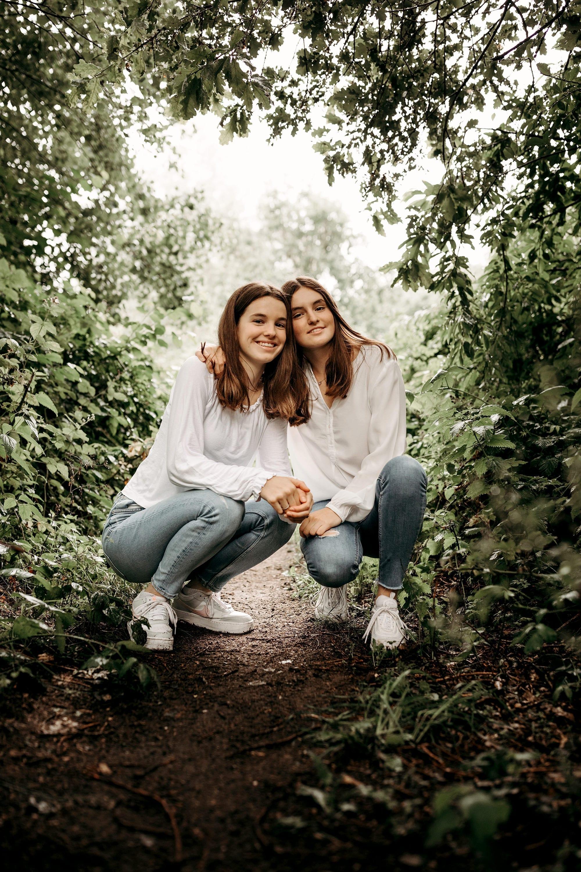 Twee bruinharige lachende jonge zussen poseren in een zussen fotosessie buiten in de Nederlandse natuur