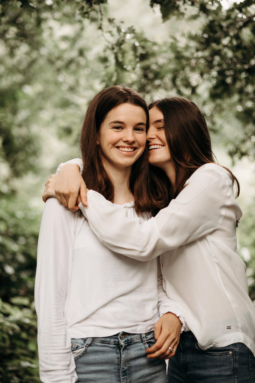 Twee bruinharige lachende jonge zussen poseren in een zussen portretfotosessie buiten in de Nederlandse natuur