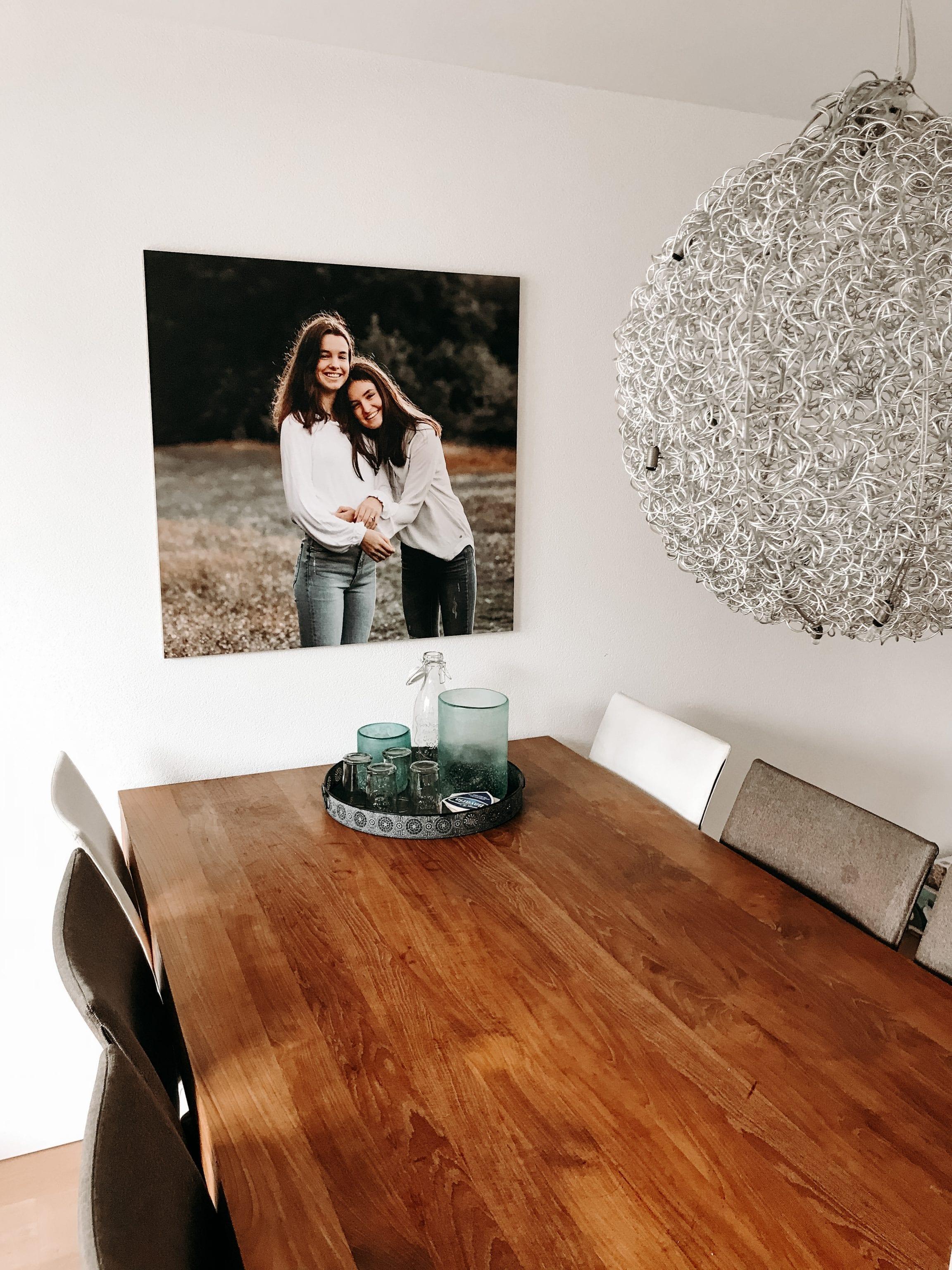 interieur foto van een groot fotoprint op de witte muur, met foto van twee zusjes genomen op een zussen fotosessie