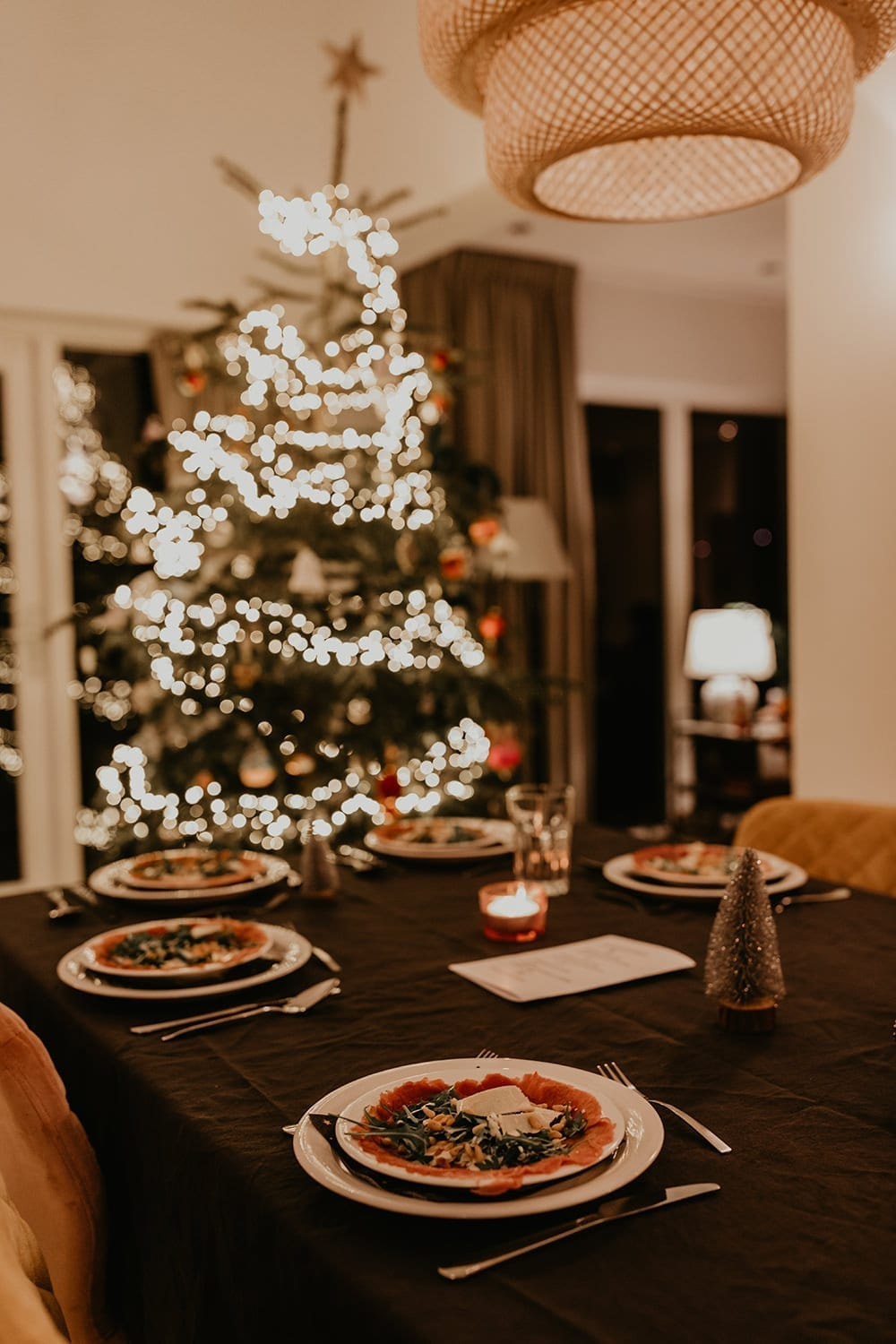 Decorated table with carpaccio and a christmas tree in the background