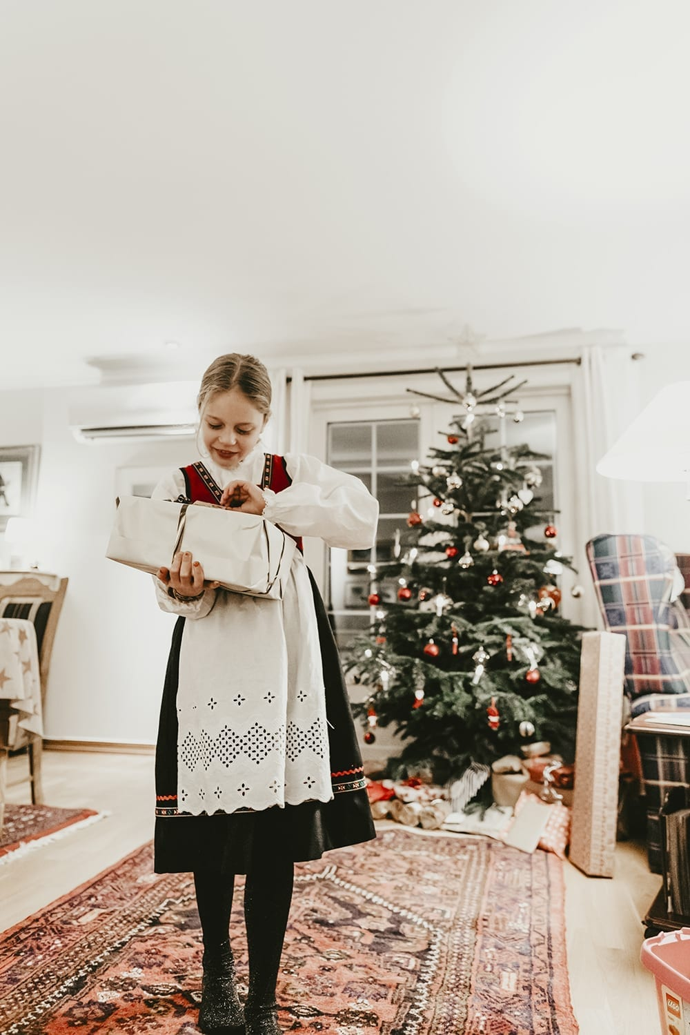 photo of girl in norwegian bunad in front of a Christmas tree, opening a gift