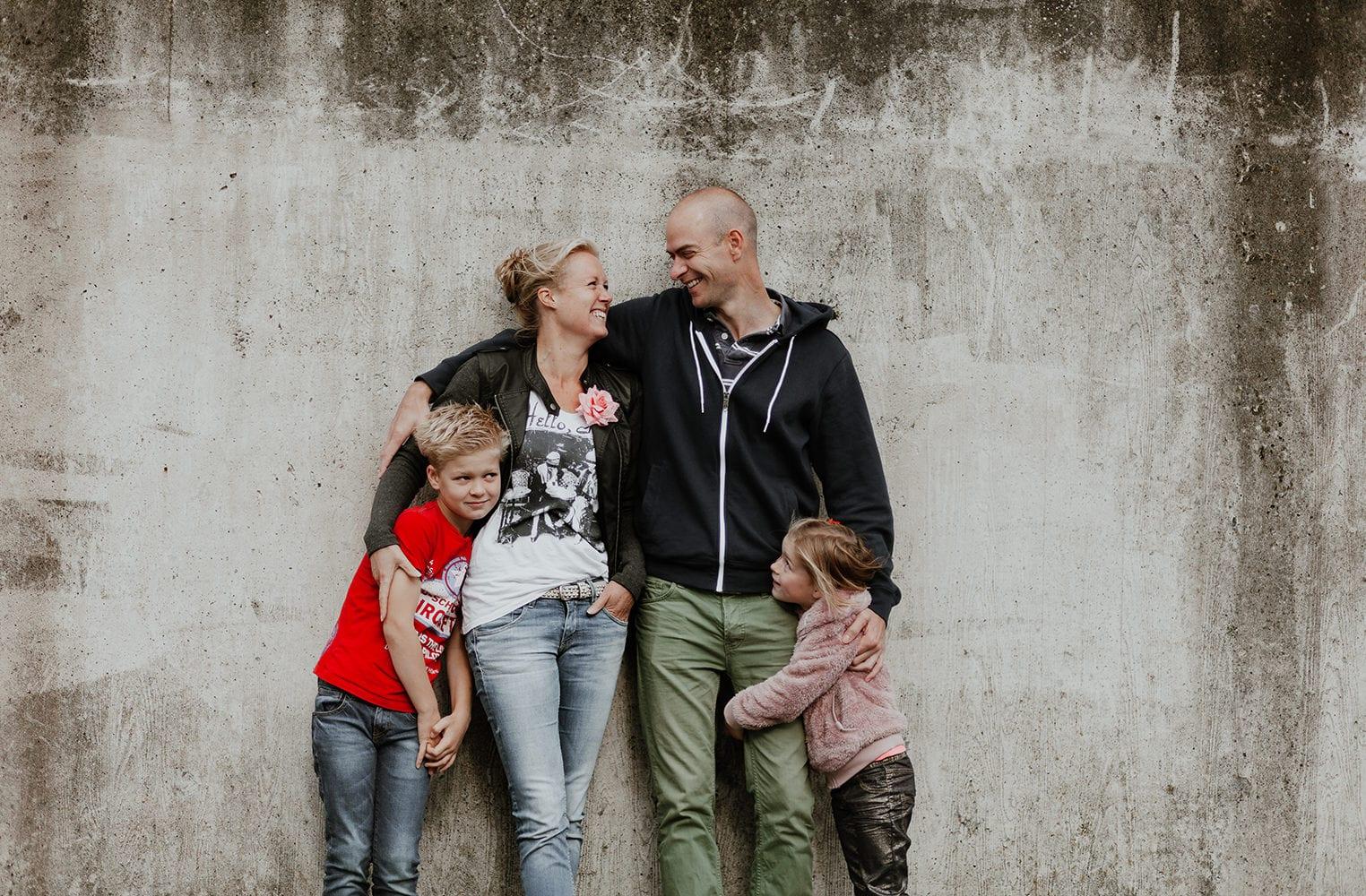 leuke familie fotoshoot, moeder, vader, jonge en meisje met een beton achtergrond