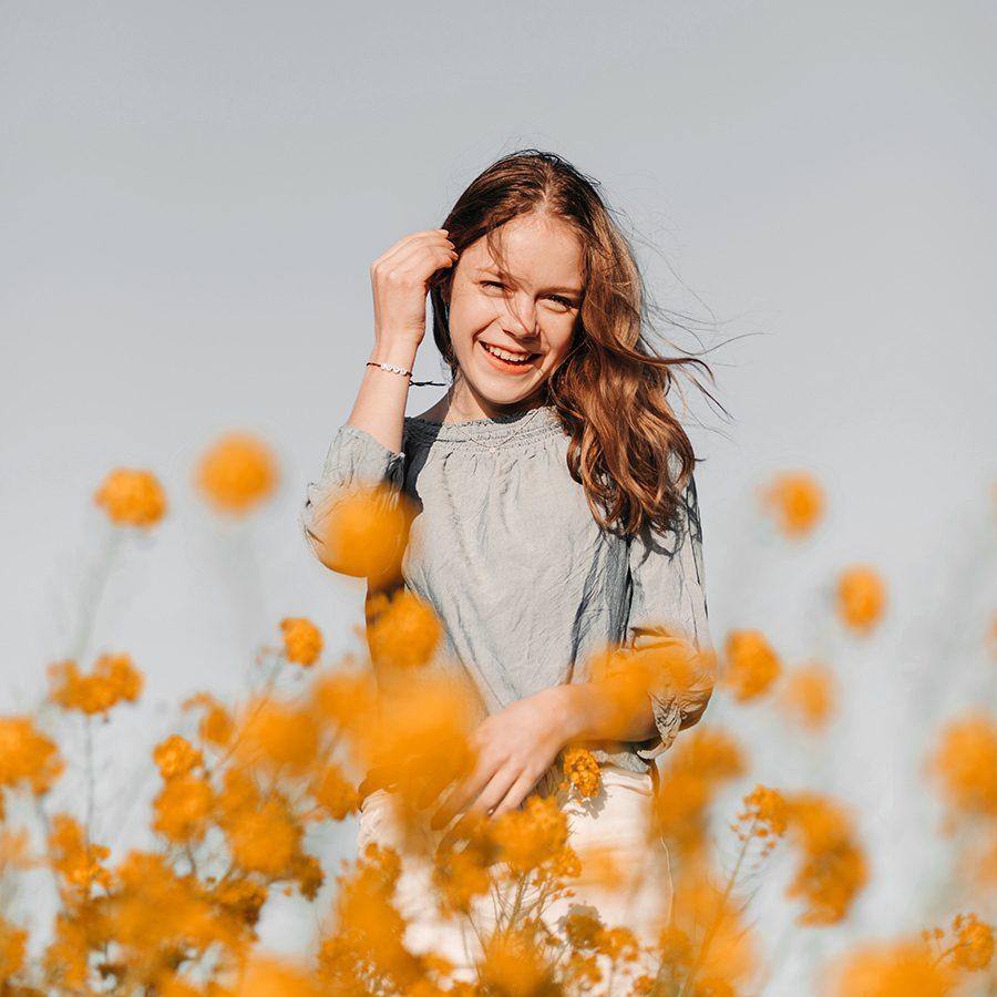 portret van gelukkig lachend meisje in een bloemenveld met gele oranje bloemen