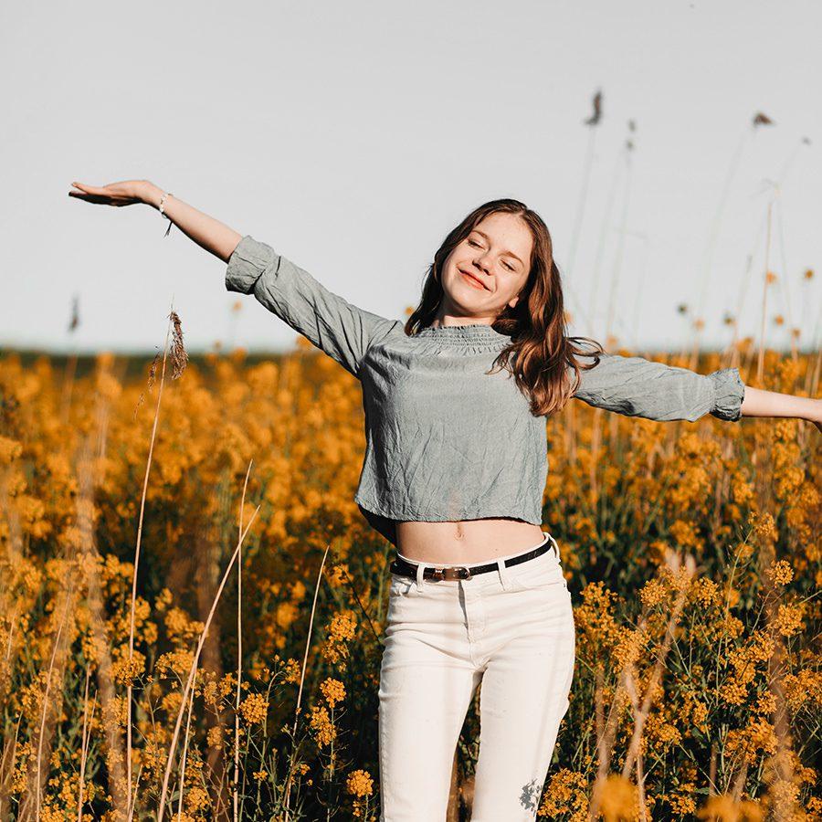 gelukkig lachend meisje in een bloemenveld met gele oranje bloemen